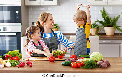 mother with children preparing vegetable salad