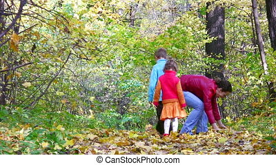 mother with children throw leaves