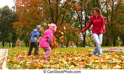 mother with children throwing autumn leaves