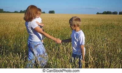 mother with children walking in field of wheat