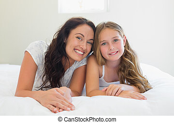 Mother with cute daughter lying in bed