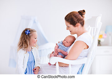 Mother with daughter and baby in a white nursery - Little...