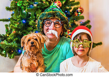 Mother with daughter and dog in new year's interior