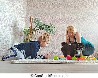 Mother with daughter and pet playing about in room during quarantine