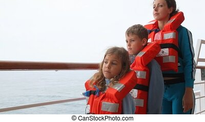 mother with daughter and son in life jackets stands on ship deck and looks afar
