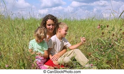 mother with daughter and son in the field, sitting in the grass