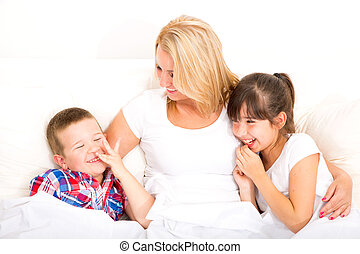 Mother with daughter and son relaxing in bed