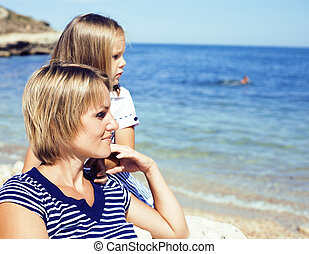 mother with daughter at sea cost together, happy real family smiling looking to horizont, lifestyle people concept, on vacations