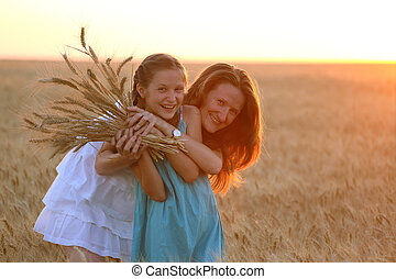 mother with daughter at the wheat field