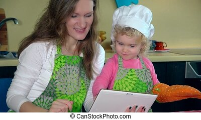mother with little curly daughter bakers looking for recipe on tablet in kitchen. 4K