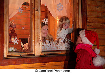 Mother with daughter behind window look at father in suit of Santa Claus