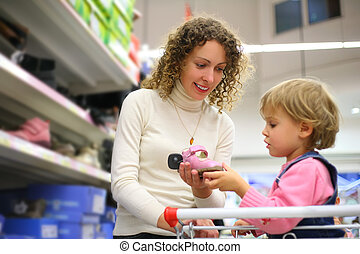 Mother with daughter choose footwear in shop