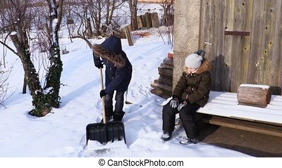 Mother with daughter clean up yard in winter morning