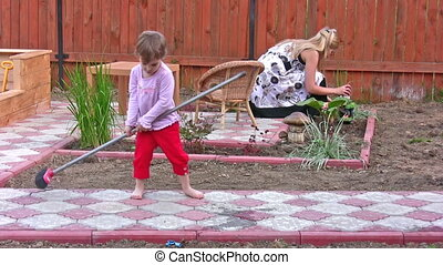 mother with daughter cleaning home yard