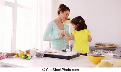 mother with daughter cooking and dancing at home - family,...