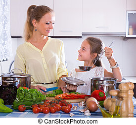 Mother with daughter cooking veggies - Cheerful mother and ...