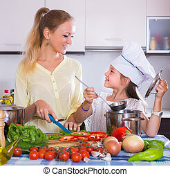 Mother with daughter cooking veggies - Cheerful young woman ...
