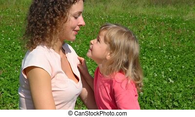 mother with daughter having fun against green grass