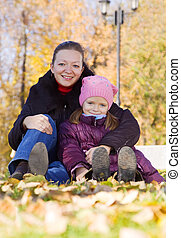 mother with daughter in autumn park
