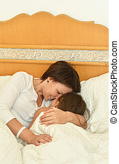 Mother with daughter in bed