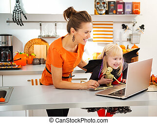 Mother with daughter in halloween bat costume having video chat