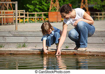 Mother with daughter in park at pool touch water