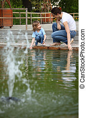 Mother with daughter in park at pool with fountain touch...