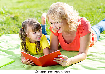 Mother with daughter in park reading book