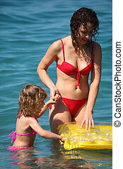Mother with daughter in sea with inflatable mattress