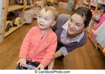 mother with daughter in toy shop