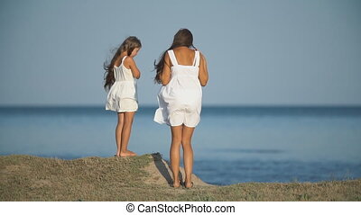mother with daughter in white dresses near the sea