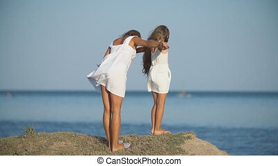 mother with daughter in white dresses walk near the sea