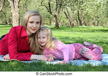 Mother with daughter lie on grass in park in spring