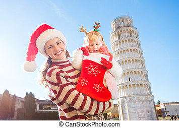 Mother with daughter looking into Christmas sock for gift, Pisa