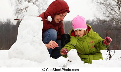 mother with daughter make face for small snowman