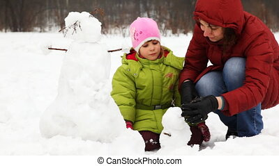 mother with daughter make small snowman