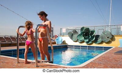 mother with daughter near swimming pool