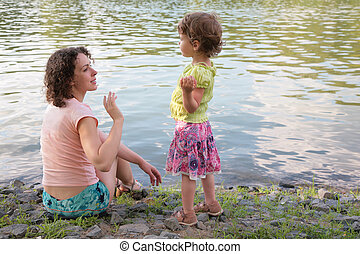 Mother with daughter near water