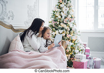 Mother With Daughter On Couch Using Tablet Computer Happy Smiling Young Family Near Decorated New Year Christmas Tree Small Girl And Woman.
