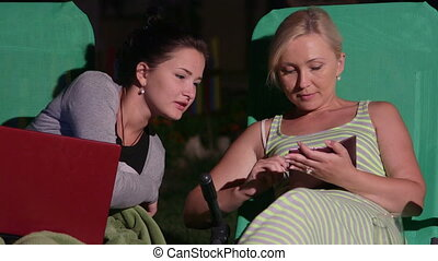 Mother with daughter on patio loungers in backyard using...