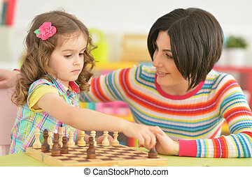 mother with daughter playing chess