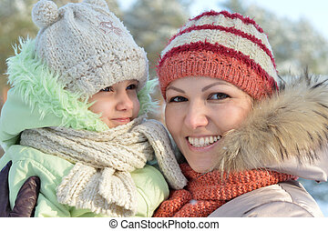 mother with daughter posing outdoors