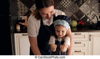 Mother with daughter prepare biscuits, girl soiled hands test and laughs.