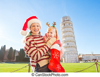 Mother with daughter pulling out gift from Christmas sock, Pisa