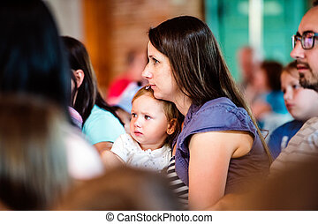 Mother with daughter sitting in a crowd of people