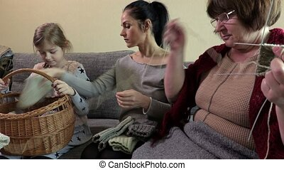 Mother with daughter sitting near grandmother who knitting
