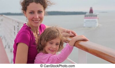 Mother with daughter stand on deck and cruiser float away