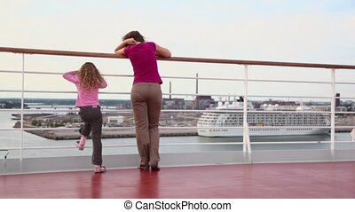 Mother with daughter stand on deck and watch vessel in port