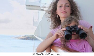 Mother with daughter stand on deck and girl watches binoculars