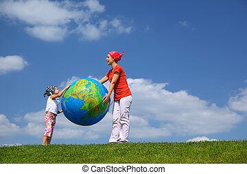 Mother with daughter stand on  grass and hold  large inflatable ball as  globe